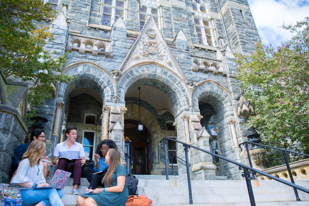 Students sitting on steps of a building on campus of Georgetown University